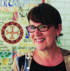 portrait of a woman with short hair and rectangular glasses. she is wearing small, dangly earrings and a top and cardigan