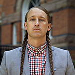 headshot of a brunette man with two braids, he is wearing a red, blue, and white plaid button-up and a gray blazer in front of a red, brick building