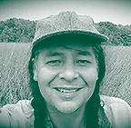 portrait of a man in braids and a hat in front of a field of grass