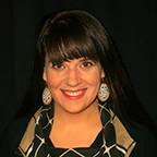 portrait of a woman with large, dark hair and bangs. she is wearing dangly earrings