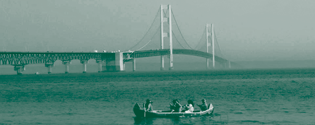 a picture of four people sitting in a canoe-like boat in a body of water, there is a large suspension bridge in the background