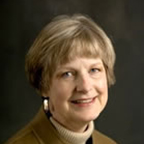 headshot of a smiling woman with light, short hair. she is wearing earrings, beige turtleneck, and a brown blazer