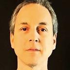 Headshot photo of a man with short hair
