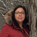 photo of a woman with long hair and rectangular glasses. She is standing by a tree with a big winter jacket on