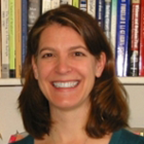 Headshot of a smiling woman with shoulder-length hair standing in front of a bookcase