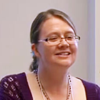 Photo of a smiling woman with tied back hair and rectangular glasses